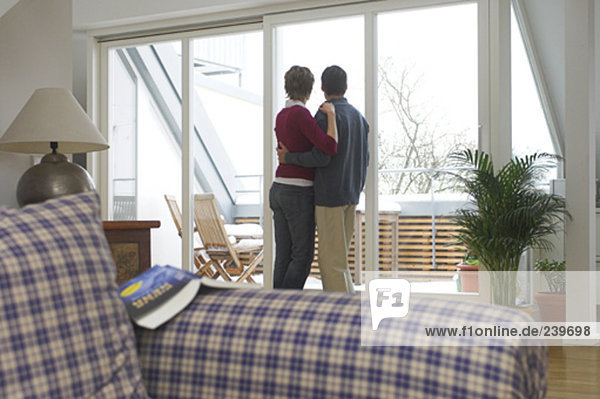 mature couple at home standing in living room looking out of the window