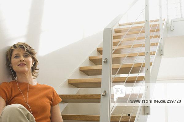 Stufe  sitzend  Interior  zu Hause  Frau  zuhören  Musik  reifer Erwachsene  reife Erwachsene