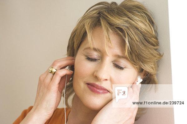 Nahaufnahme Frau an Wand gelehnt und Musik zu hören