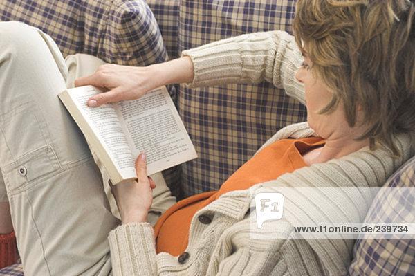 Rückansicht Frau Lektüre auf sofa