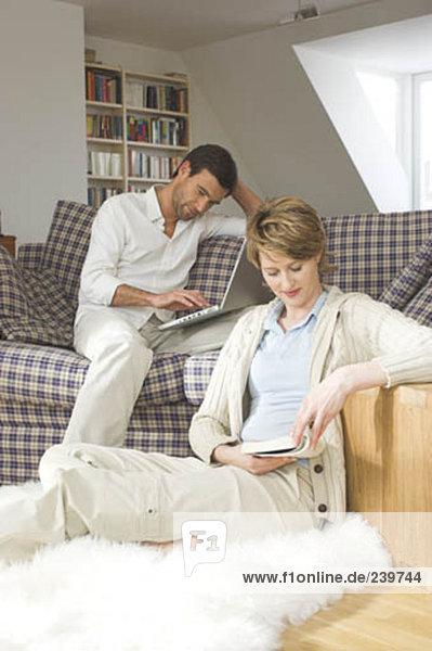 paar sitzen im Wohnzimmer Frau lesen und Man die Arbeit mit Computer zusammen