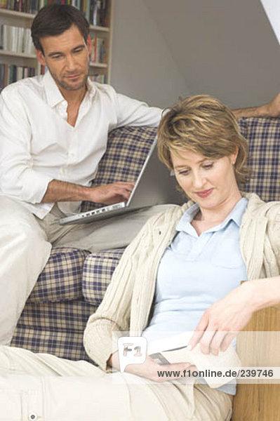 Mann  Notebook  sehen  Ehefrau  Buch  reifer Erwachsene  reife Erwachsene  cocooning  Taschenbuch  vorlesen