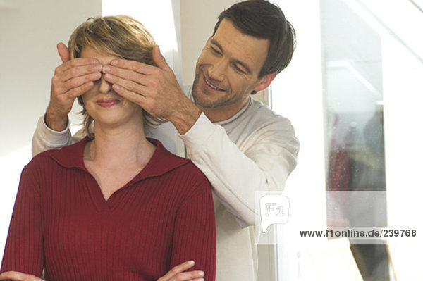 mature couple playing peekaboo  man covering woman´s eyes for a surprise