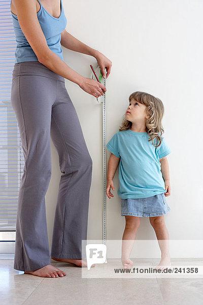 Mutter misst die Höhe der Töchter