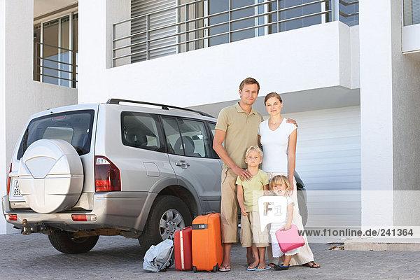 Familie stand bei Auto mit Koffer