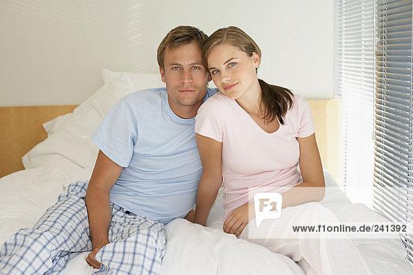 Porträt eines erwachsenen Paares auf dem Bett sitzend
