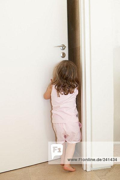 Junges Mädchen schiebt eine Tür auf
