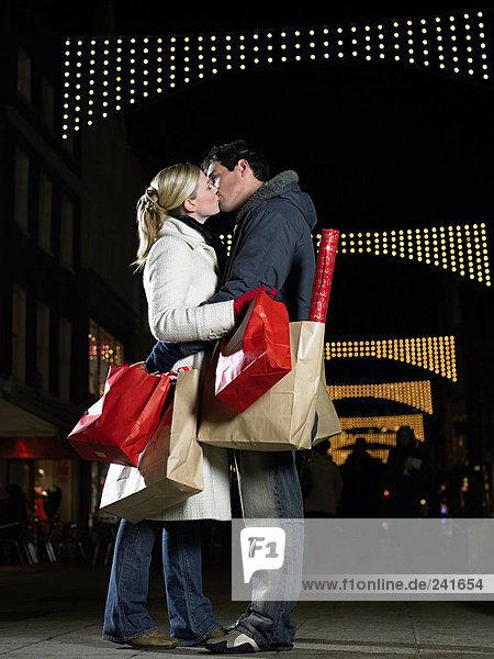 Pärchenküssen beim Weihnachtseinkaufen