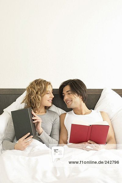 Junges Paar liegt im Bett und liest  fully_released