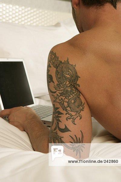 Mann mit freiem Oberkörper und einem großen Tattoo liegt auf dem Bett mit einem Laptop,  fully_released