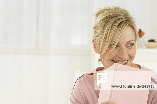 Junge blonde Frau lacht verträumt mit einem Buch vor dem Kinn - Lesen  fully_released