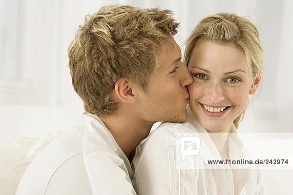 Junges blondes Paar  Mann umarmt Frau von hinten und küsst sie auf die Backe - Partnerschaft  fully_released