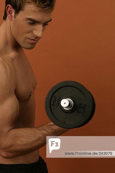 Ein Mann trainiert mit Gewichten  fully_released