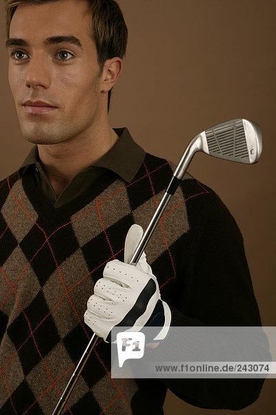 Ein Golfspieler hält ein Eisen in der Hand  fully_released