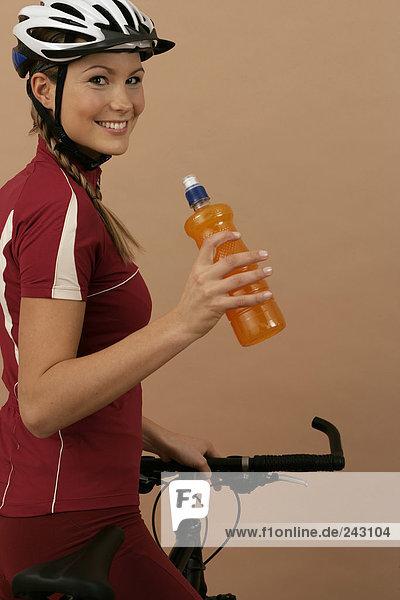 Mountainbikerin hält eine Flasche in der Hand und blickt in die Kamera  fully_released