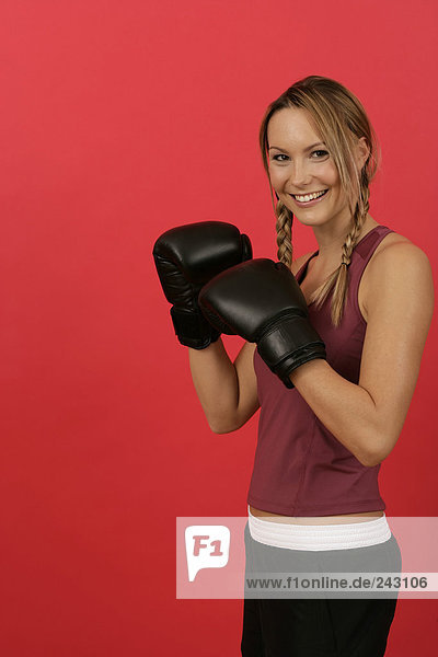 Junge Frau in Sportkleidung mit Boxhandschuhen  fully_released
