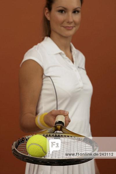 Tennisspielerin balanciert einen Ball auf dem Schläger  fully_released
