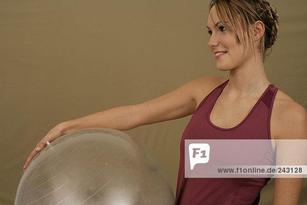 Junge Frau hält einen Gymnastikball im Arm  fully_released