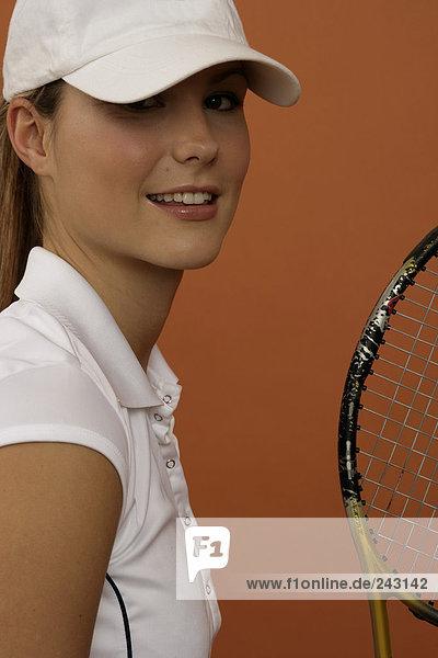Tennisspielerin mit Basecap und Schläger blickt in die Kamera  fully_released