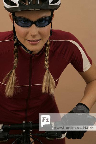 Mountainbikerin mit Schutzhelm und Sonnenbrille blickt in die Kamera  fully_released