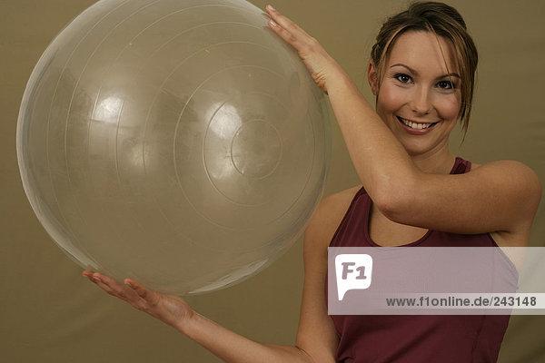 Junge Frau hält einen Gymnastikball zwischen den Händen  fully_released