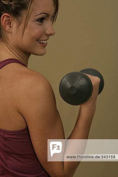 Junge Frau trainiert mit Gewichten  fully_released