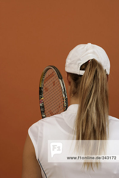 Rückansicht einer Tennisspielerin mit Basecape und Tennisschläger  fully_released