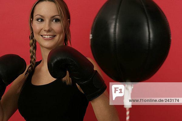 Boxerin trainiert mit einem Punchingball  fully_released
