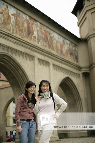 Two young Asian women standing in front of a painted gate  selective focus
