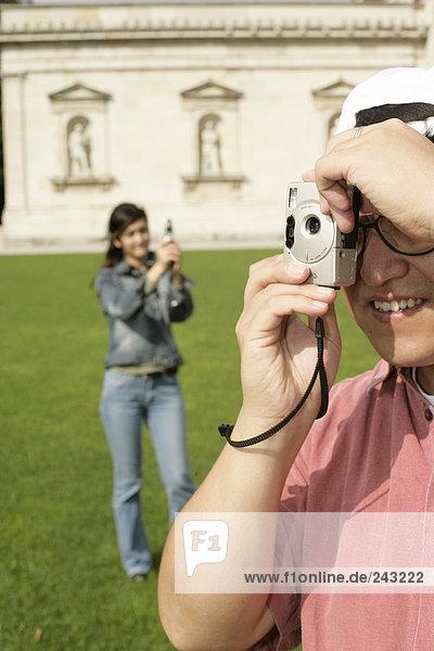 Asiatischer Mann mit Cap steht fotografierend vor einer Asiatin mit einem Handy in einem Park - Tourismus  fully_released