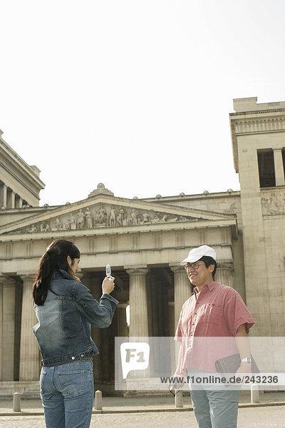 Asiatischer Mann mit Cap wird von einer Frau vor einem antiken Gebäude fotografiert - Tourismus  fully_released
