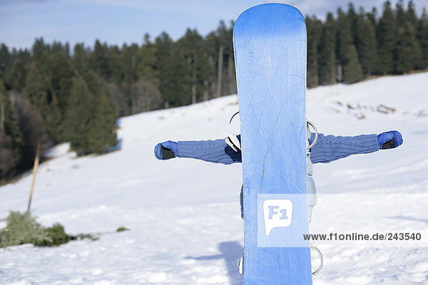 Junge steht hinter einem Snowboard  fully_released