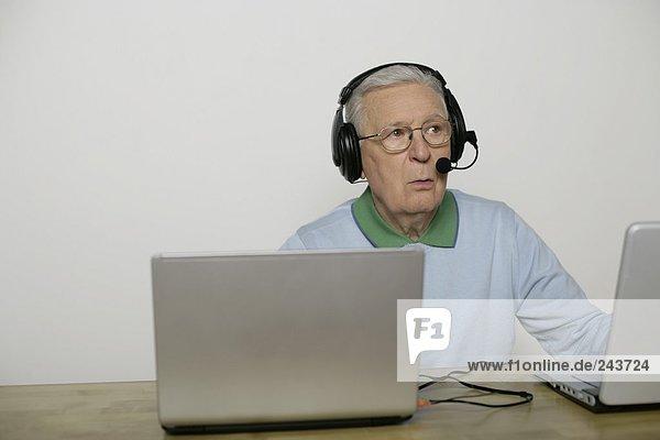 Alter Mann sitzt mit einem Headset vor einem Laptop  fully_released
