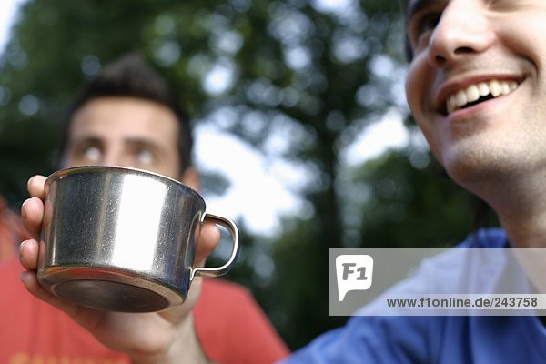 Young man holding a cup (camping dishes) in his hand  focus on cup
