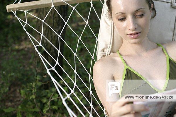 Junge Frau liest in einer Hängematte in einer Zeitschrift  fully_released