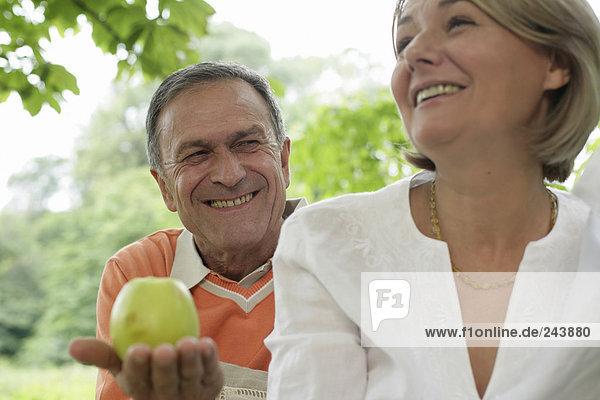 Grinsender älterer Mann reicht Frau einen Apfel  fully_released