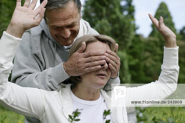 Älterer Mann hält Frau die Augen zu  fully_released