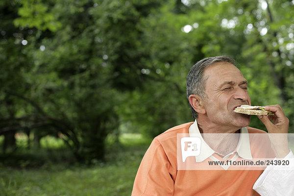 Älterer Mann isst ein Sandwich  fully_released