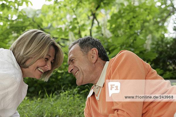 Älteres Paar liegt im Grass  lacht und sieht sich in die Augen  fully_released