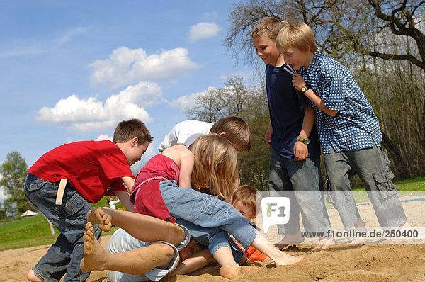 Children (6-9) play fighting on playground