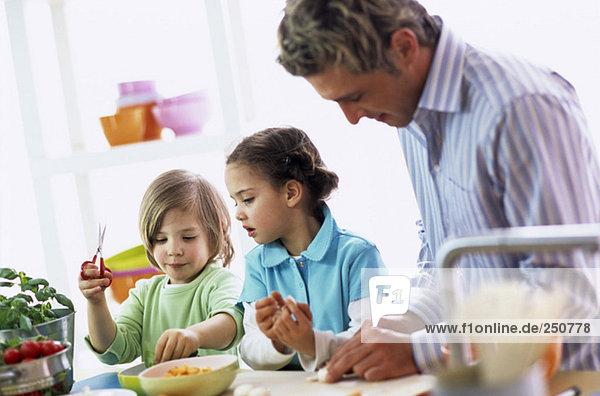 Vater mit Kindern (4-7) beim Zubereiten des Essens