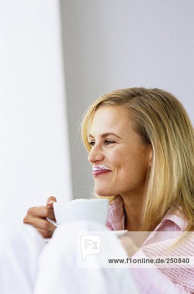 Frau hält Kaffeetasse  lächelnd  wegschauend