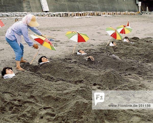 10046381  Ibusuki  Japan  Asien  Patienten  Krankenschwester  Sand  gegraben  sand begraben  Sonnenschirme  Strand  Meer  Bad  Wellness