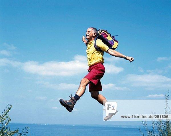 10422250  walking  Wandern  trekking  aktiv  Fitness  lachen  caper  springen  Senioren  Küste  Meer  See  Rucksack
