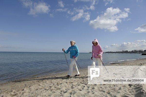 Zwei ältere Frauen machen Nordic Walking am Ostseestrand  fully_released