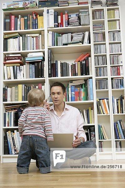 Sohn steht vor Vater  der mit einem Laptop und einem Handy vor einem Bücherregal sitzt  fully_released