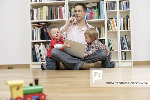 Vater mit zwei Söhnen versucht zu telefonieren und am Laptop zu arbeiten  fully_released