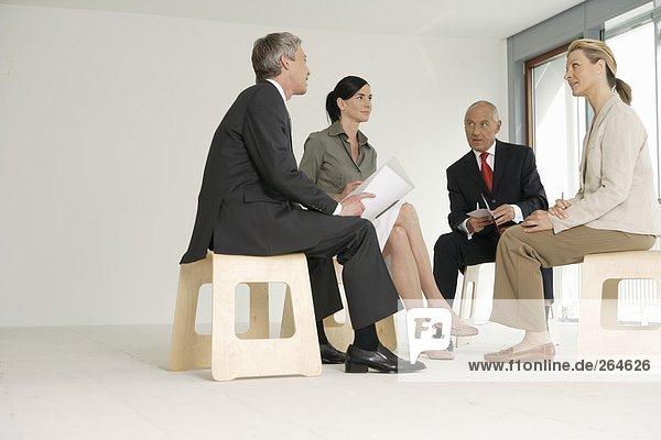 Gruppe von Geschäftsleuten sitzt auf Hockern in einem leeren Büro  fully_released
