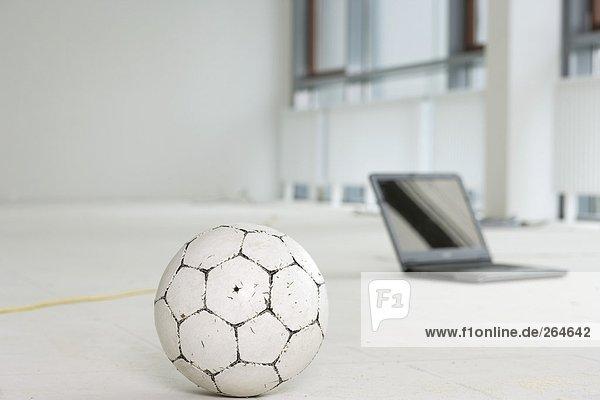 Laptop und Fußball auf dem Fußboden in einem leeren Büro  fully_released