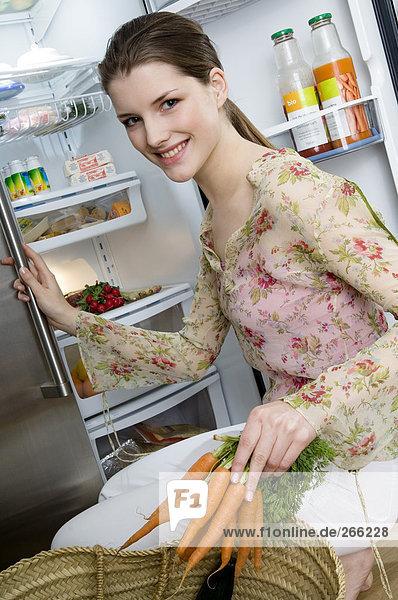 Frau vor dem Kühlschrank